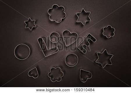 Cookie cutters shaped in Love on black background. Baking cookies concept.