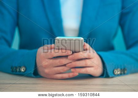 Businesswoman using smartphone close up female person hands in elegant blue business suit holding mobile phone selective focus