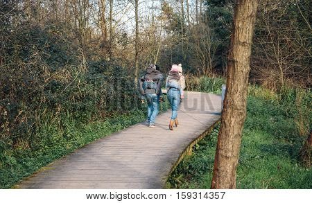 Back view of parents giving piggyback ride to children while running over a wooden pathway into the forest