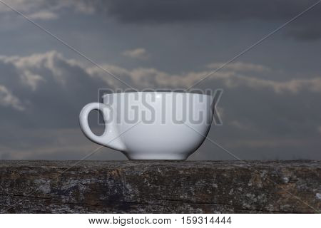 Cup of coffee or tea on wooden table with sky view. Side view