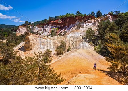 The elderly woman photographs the landscape. Orange and red picturesque hills in Roussillon