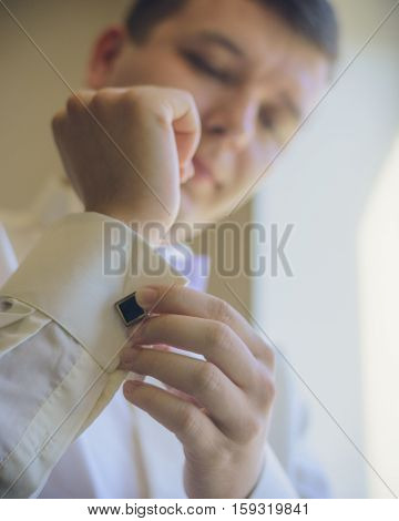 Man buttons dark cufflinks on the sleeves