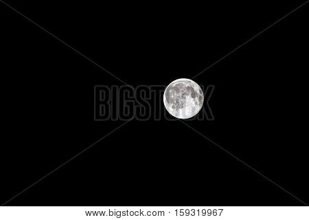 View of a full silver moon in the night sky.