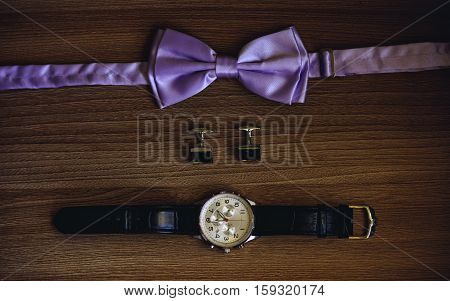 Bow-tie, cufflinks and watches on wooden background