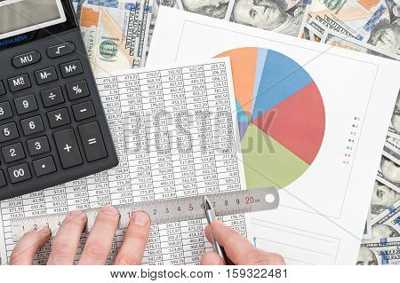 Man put a ruler to the table with numbers located on the dollar background