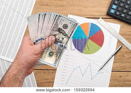 Male hand holding a lot of money over a wooden table with calculator and business charts
