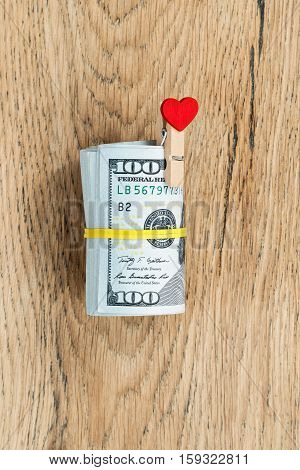 Roll of dollars tied yellow rubber, with a gift in the form clothespin of a red heart on a wooden table