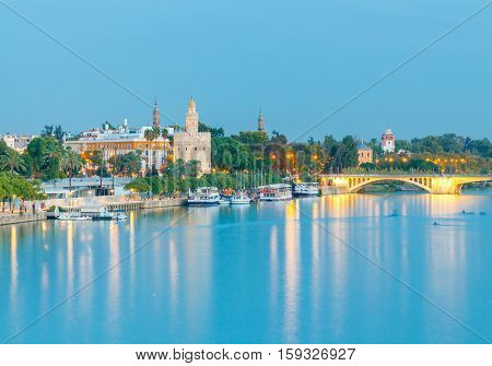 Night view of the Golden Tower on the waterfront of the Guadalquivir. Sevilla. Andalusia.