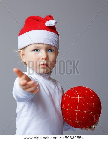 Portrait of Caucasian baby with blue eyes wearing a Santa hat and white shirt standing on a light background holding red golden chinese ball and giving welcome hand New Year concept studio