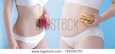 fat overweight woman and slim woman take apple and hambuger isolated on blue background asian