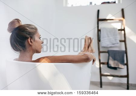 Young Woman Lying In Bathtub And Looking Away