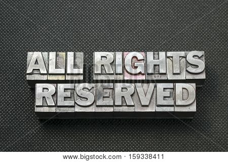 all rights reserved phrase made from metallic letterpress blocks on black perforated surface