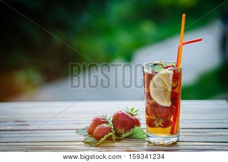 Glass of cold tea with mint, strawberry, lemon, on table, on green background, soft focus.