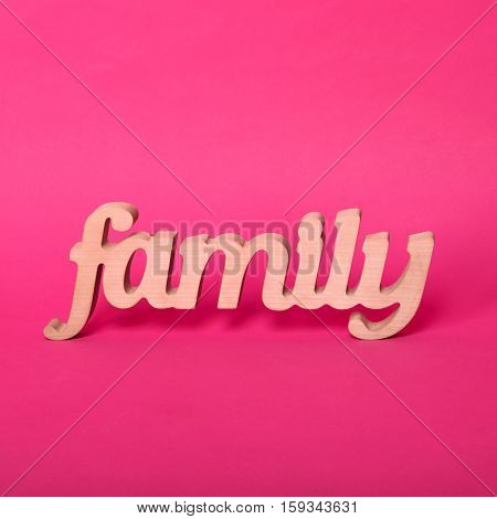 Word family, wooden letters on pink paper background. Love and unity concept