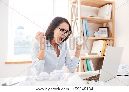 Picture of angry businesswoman dressed in white shirt sitting in her office and screaming while tear paper. Look at laptop.