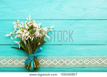 Valentines day. Fresh bouquet of flowers and lace ribbon on blue wooden background. Top view