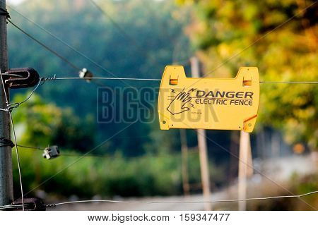 Danger electric fence sign on a wire fence in jungle. These provide protection to villages in India from wild animals.
