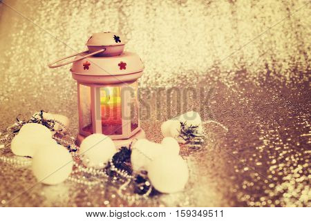 Lantern with burning candle stands in the corner of a silver blurred background surrounded by Christmas-tree decorations and garlands. Preparing for Christmas. Copy space. Front view.