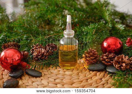 Christmas fir tree with oil and stones on wicker woven mat on mat