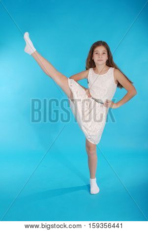 Cheerful young girl pretty tomboy raising her leg isolated on blue