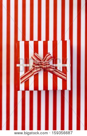high-angle shot of an elegant gift wrapped in a red and white striped-patterned paper and topped with a ribbon bow of red and white striped-patterned, on a red and white striped-patterned background