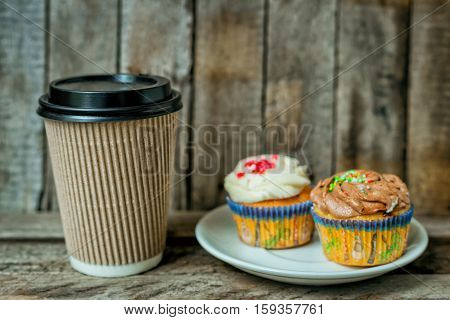 Cappuccino, coffee and cupcake in rustic style on wooden table