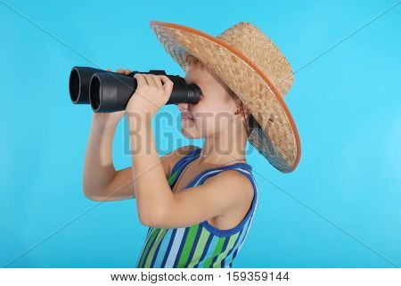 Curious boy in cowboy hat looking through binoculars. Photo on a blue background