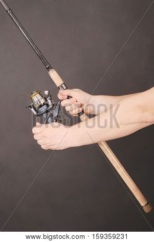Man's hand holding a fishing rod on a black background