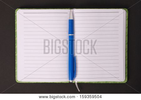 Green open notebook with blue pen isolated on black background red soft shadow