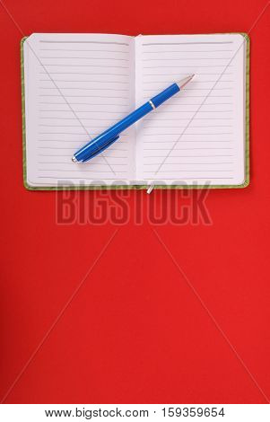 Green notebook with blue pen isolated on red background with soft shadow place for your text