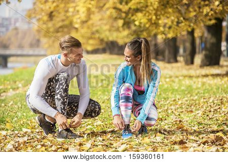 Beautiful Young Couple Preparing Their Shoes For Run In The Park. Autumn Environment.