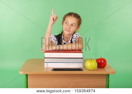 Girl in a school uniform raising hand to ask question isolated on green