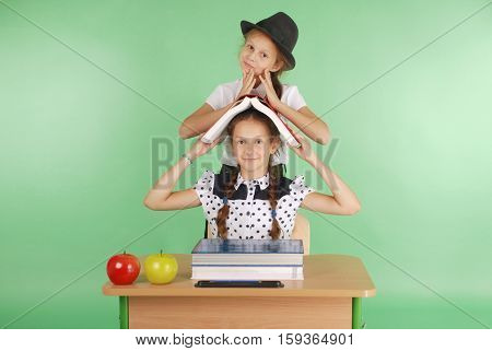 Two girl in a school uniform sitting at a desk and reading a book isolated on green