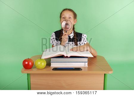 Girl in a school uniform sitting at a desk with a magnifying glass isolated on green