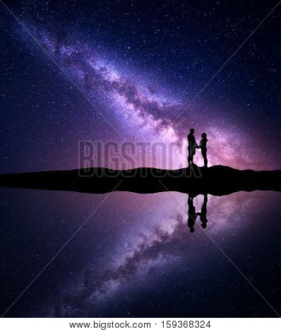 Milky Way with silhouette of people. Landscape with night starry sky and man and woman holding hands on the mountain near the lake with reflection in water. Hugging couple with milky way. Universe
