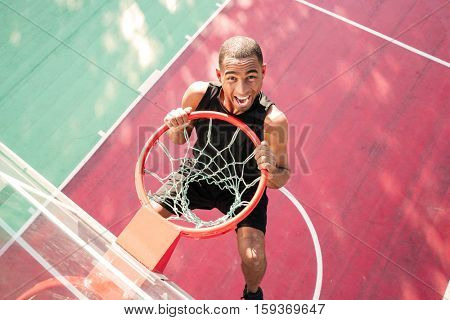 Image of young screaming african basketball player practicing. Looking at camera.