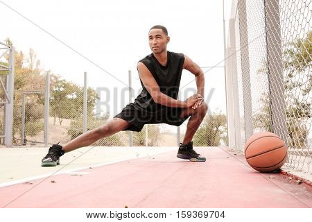 Photo of young african basketball player making sport exercises. Shooting at basket outdoor. Look aside.