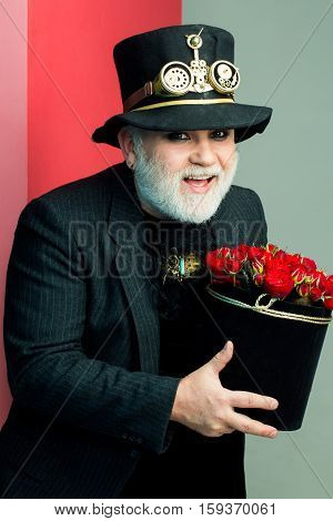 Smiling senior bearded man or watchmaker with white beard in black hat with watch mechanical metallic gears and cogwheels holds box with flowers on colorful wall