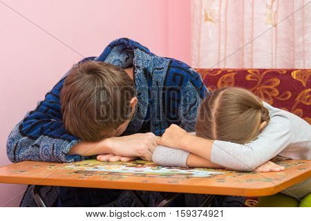 Dad And Daughter Fell Asleep At The Table Collecting Picture Of Puzzles