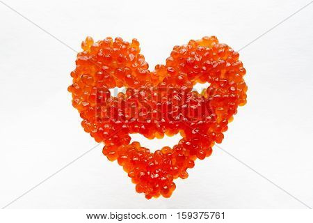 Smiling heart made of red caviar. Small red kechuzh' roe laid in the form of heart. Delicious! And it is a symbol of the New Year and Valentine's Day.