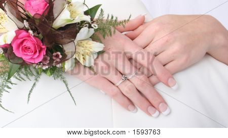 Female Hands Held Together Showing Off Rings And Flowers