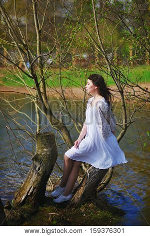 Cute romantic long-haired brunette girl in a white dress and a bright cardigan resting on a stump on the shore of the lake on the background of blossoming branches on a Sunny spring day.
