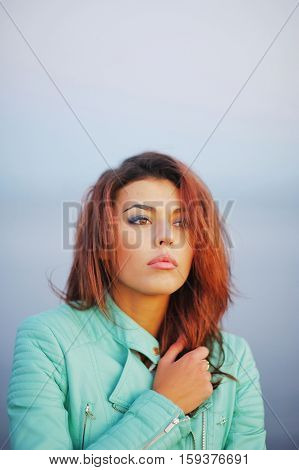 Portrait of beautiful brown-eyed girl brown-haired in turquoise blue leather jacket shivering from the cold wind on blurred background closeup