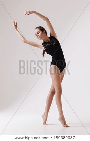 young beautiful barefoot woman dancer in black swimsuit on a light gray studio background