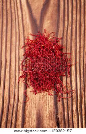 saffron spice in pile on old wooden background, closeup