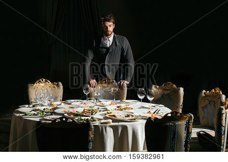 Handsome Man Stands Over Table