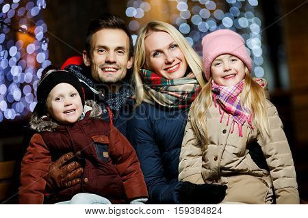 Parents with children on bench in street in winter against backdrop lights windows