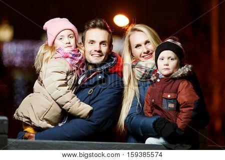 Festive family on walk in evening in winter