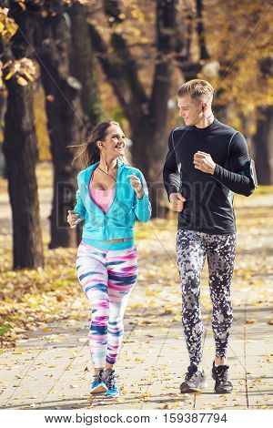 Beautiful Young Couple Running Together In The Park. Autumn Environment.