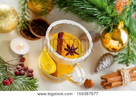 Glass of mulled cider by Christmas tree with decorations. Traditional hot drink. Top view.